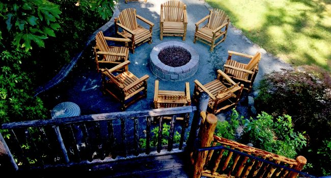 The balcony of Lodge Room #5 overlooks the fire-pit and grounds